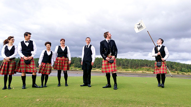 kilted staff on a golf green, one holding a flag pole with the Skibo castle logo